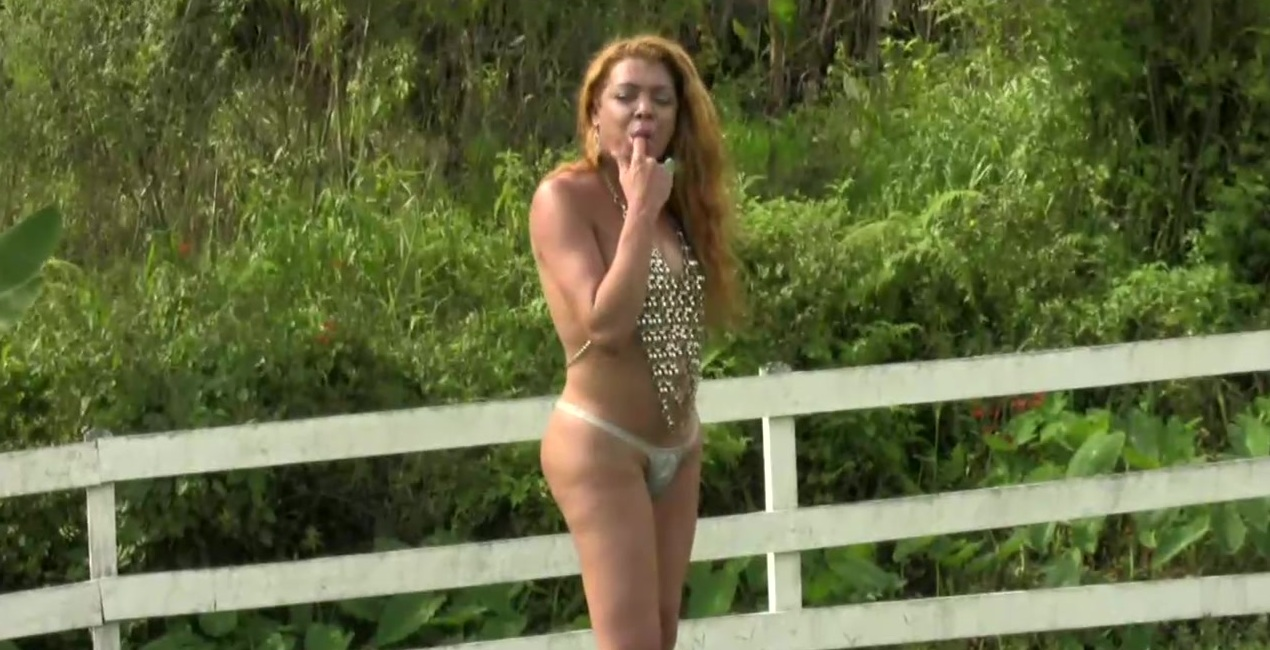 Curly shemale is masturbating and swinging big cock outdoors